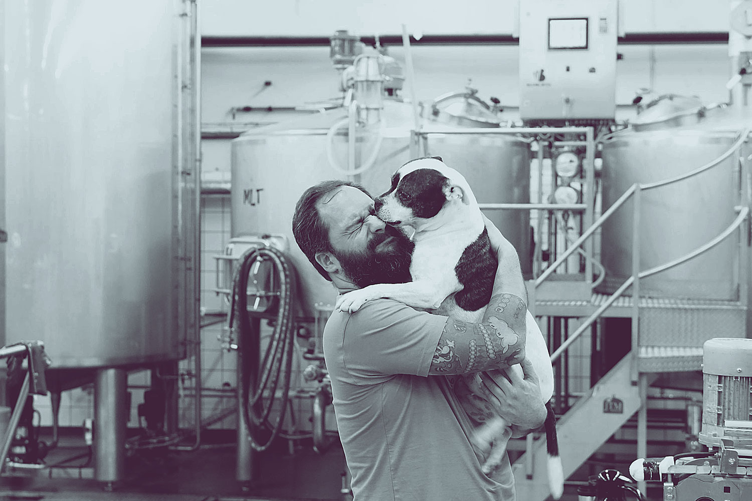 Magnus Svensson from Benchwarmer's Brewing hugging Cookie, one of the dogs at Beerbliotek Brewery.