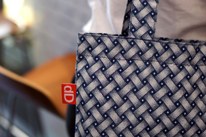 A designer bag hanging around the shoulder of a female model, designed by Darryl de Necker for Darryl Design and made of Shweshwe.